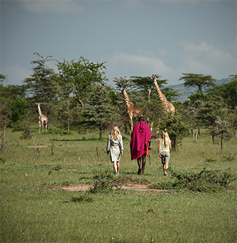 Cottar children walking with a representative of the Maasai community